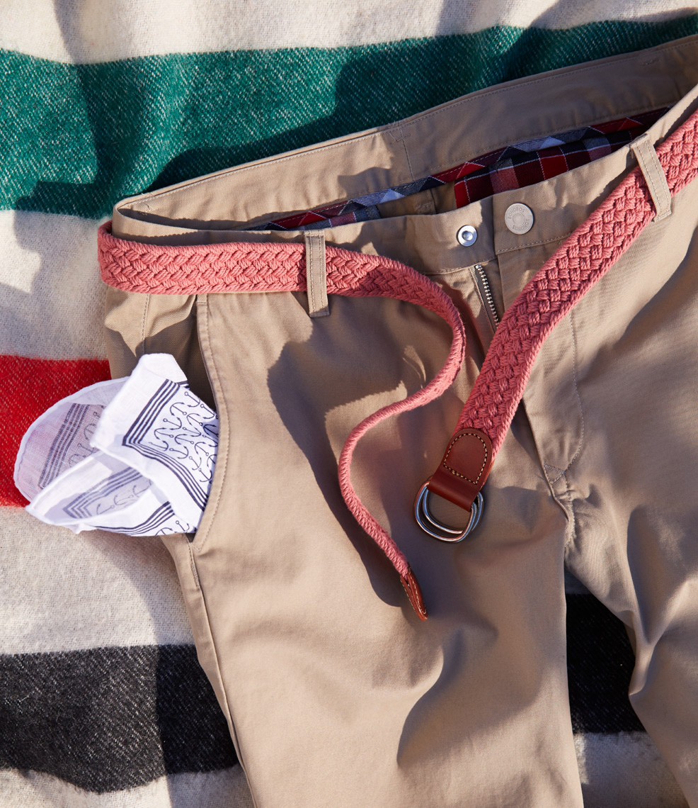tan pants with white handkerchief in pocket and red stitched belt on striped blanket