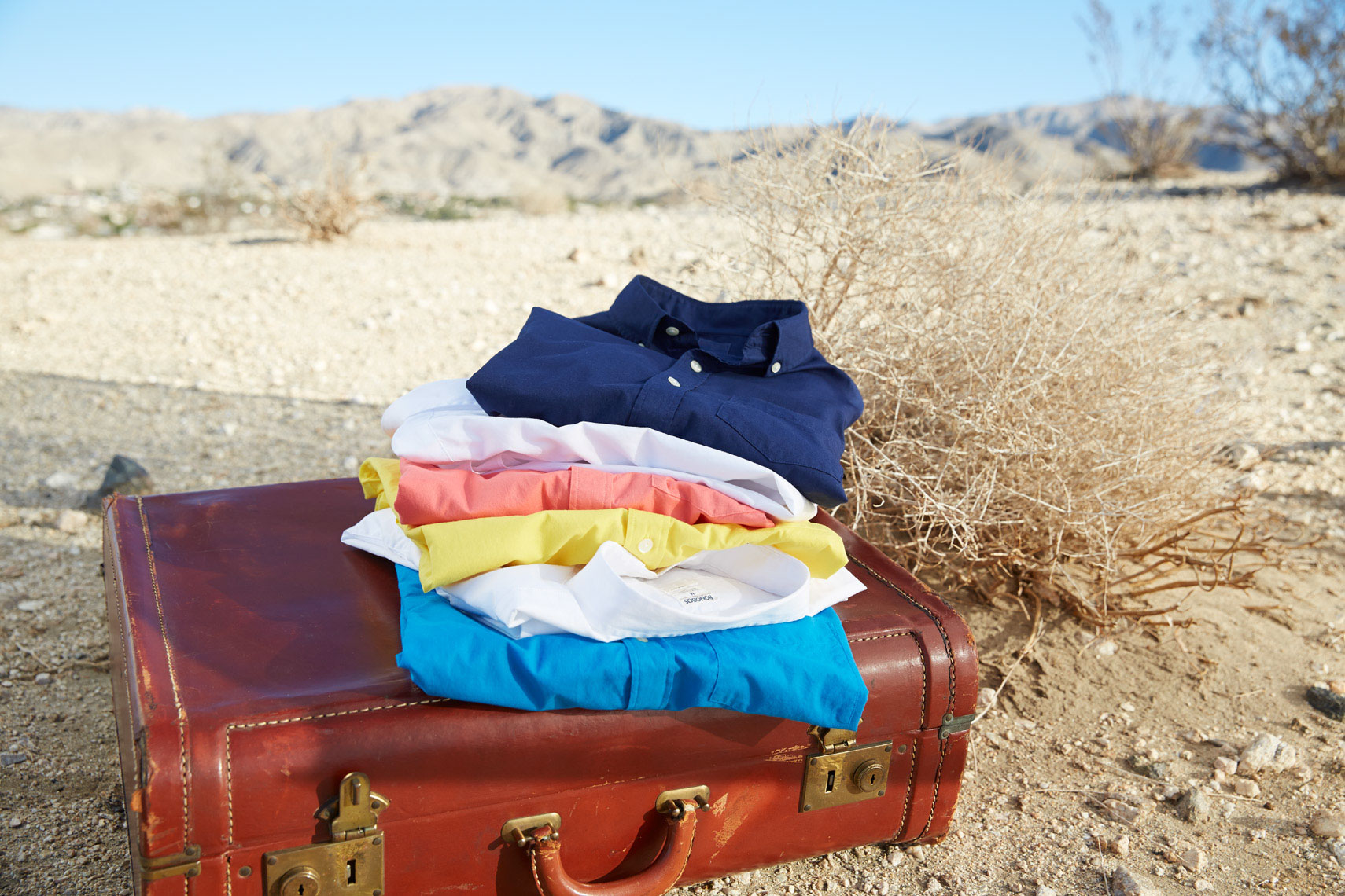 folded colorful summer button-up shirts on brown leather briefcase in sandy desert