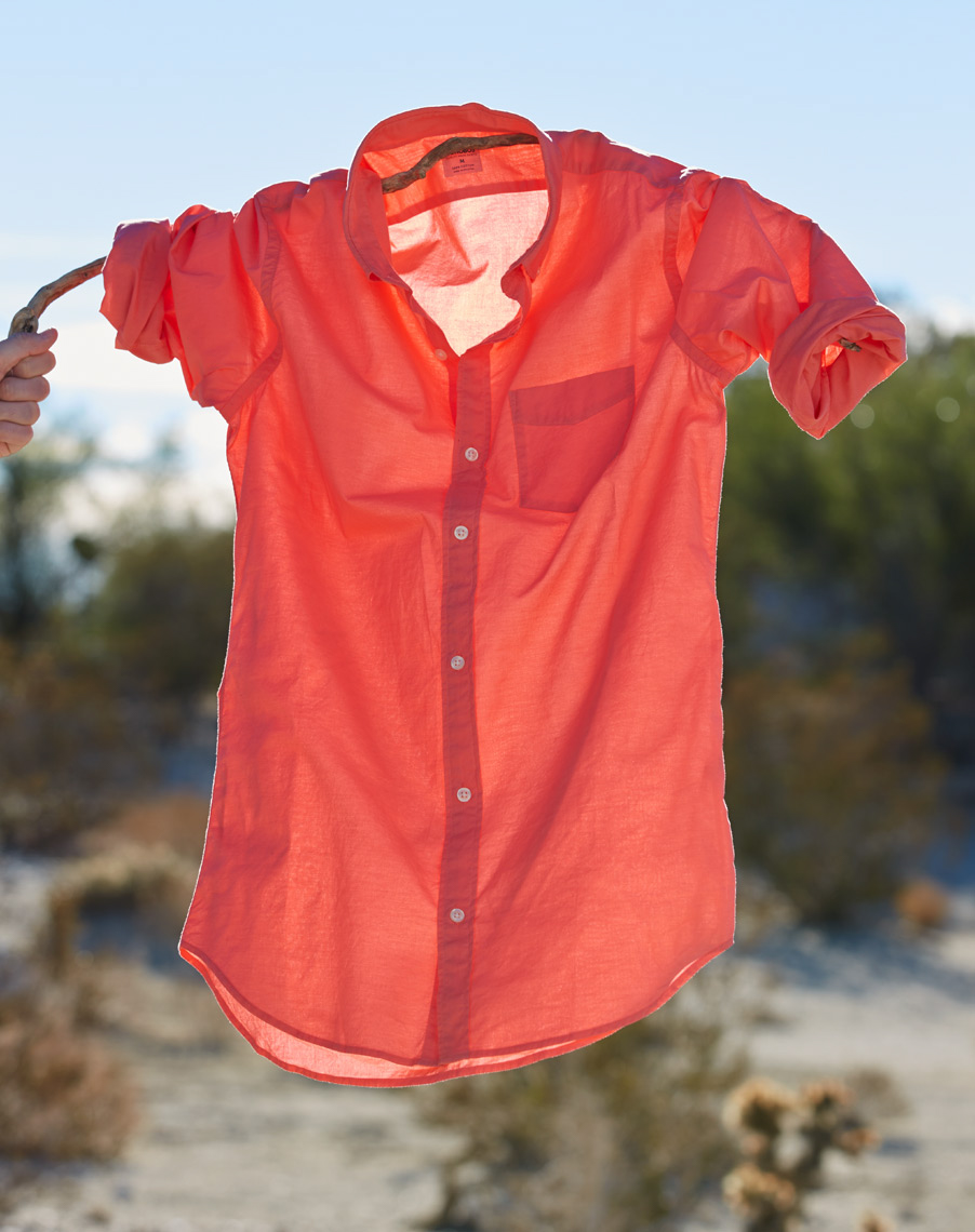 red summer shirt hanging from branch held up by hand with desert scene background