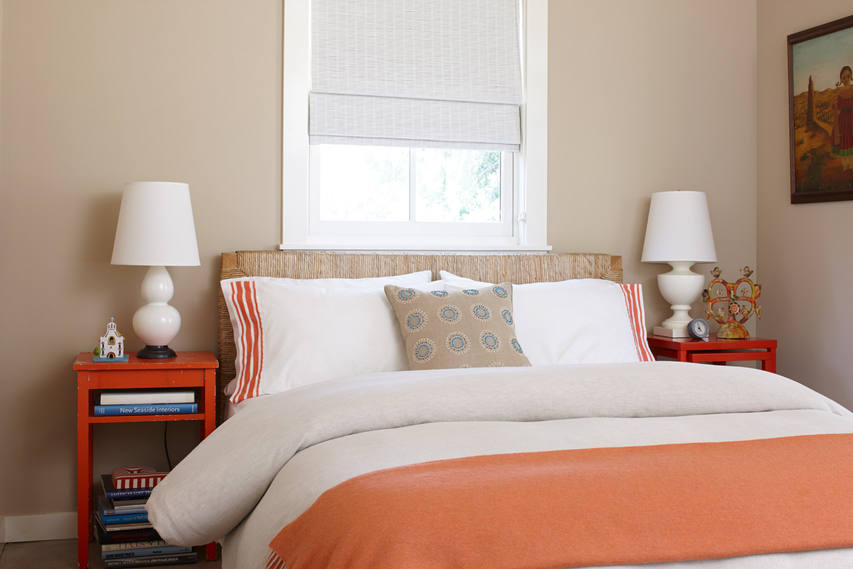 bedroom with orange and white bedspread with red bedside tables and white lamps