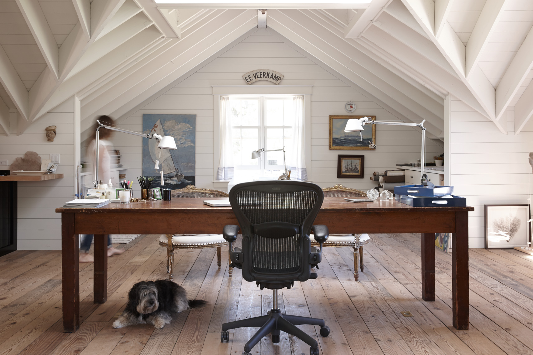 home attic office space with black wheeled chair and a shaggy dog under long wooden table