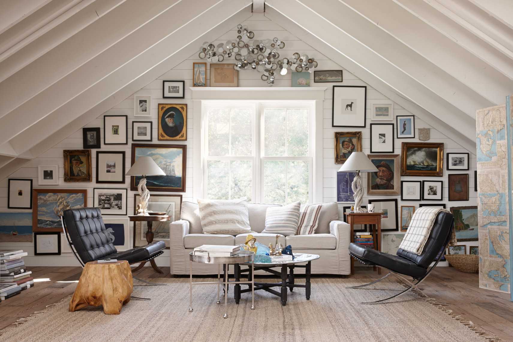 home attic a-frame living space with window and framed pictures on wall and white sofa between 2 black chairs