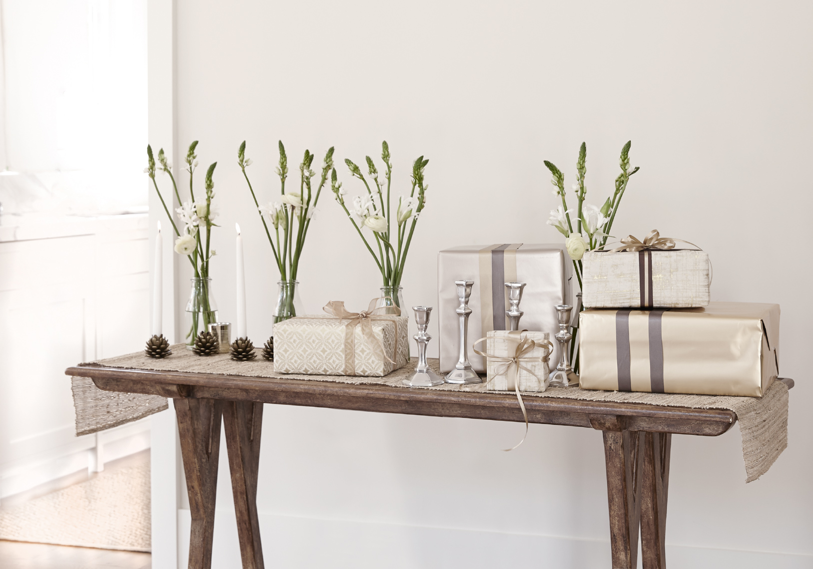 wedding gifts and candlesticks on thin wooden table with beige table-runner San Francisco interior photographer