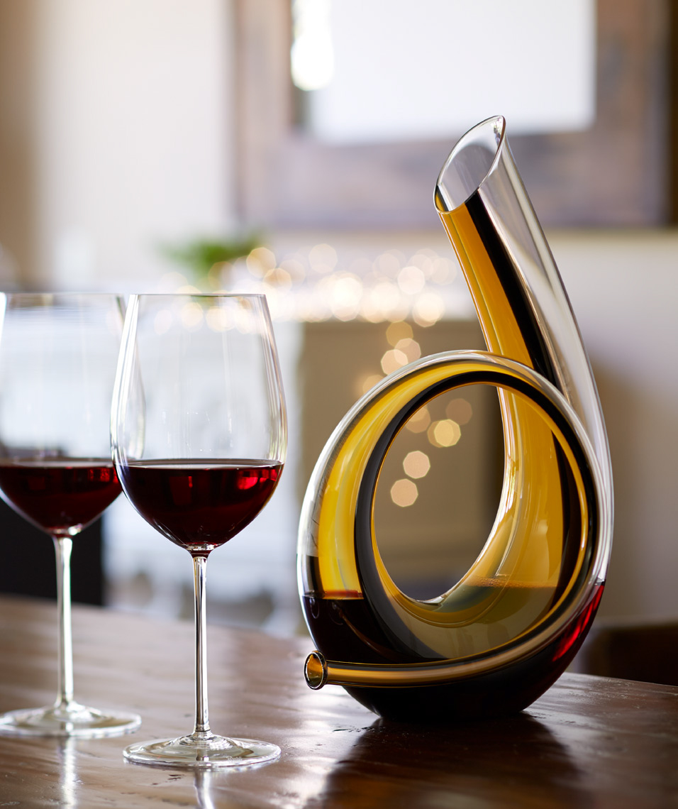 2 glasses of wine with decorative beverage container in warm lit dining room
