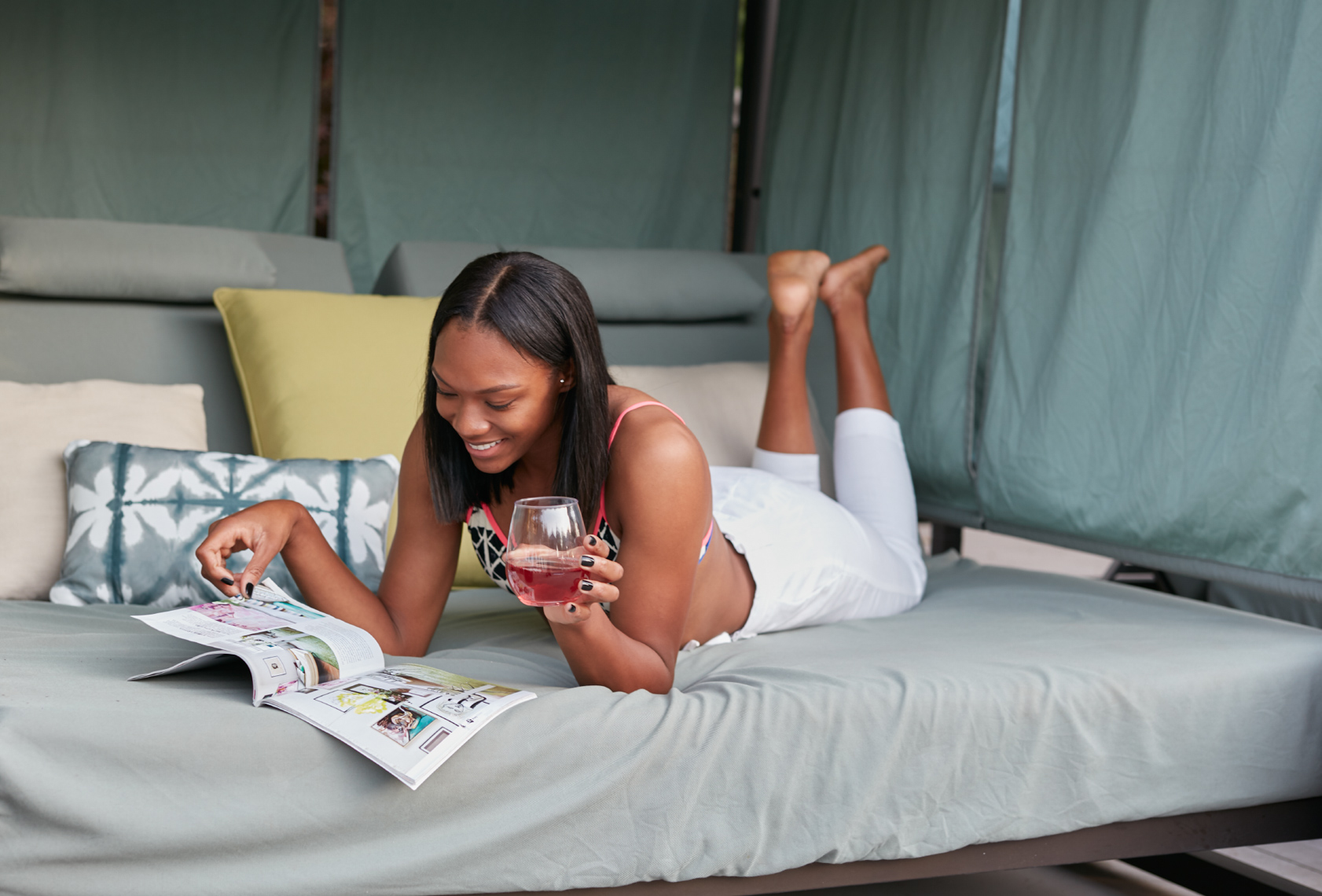 Woman with cocktail reading a magazine in green cabana with pillows