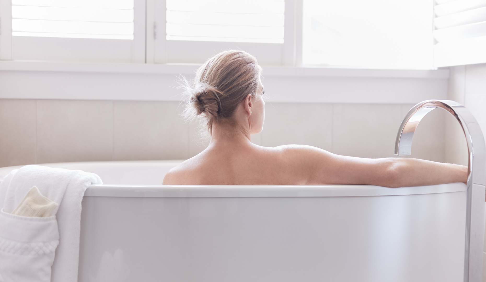 Woman from behind sitting in white bath tub with bare arm on edge of tub glancing out window