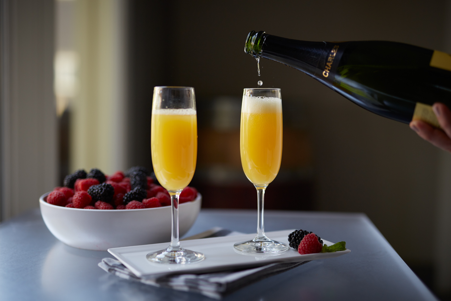 Champagne being poured into orange juice mimosas with bowl of fruit  shot for Senza Hotel and Spa in Napa California