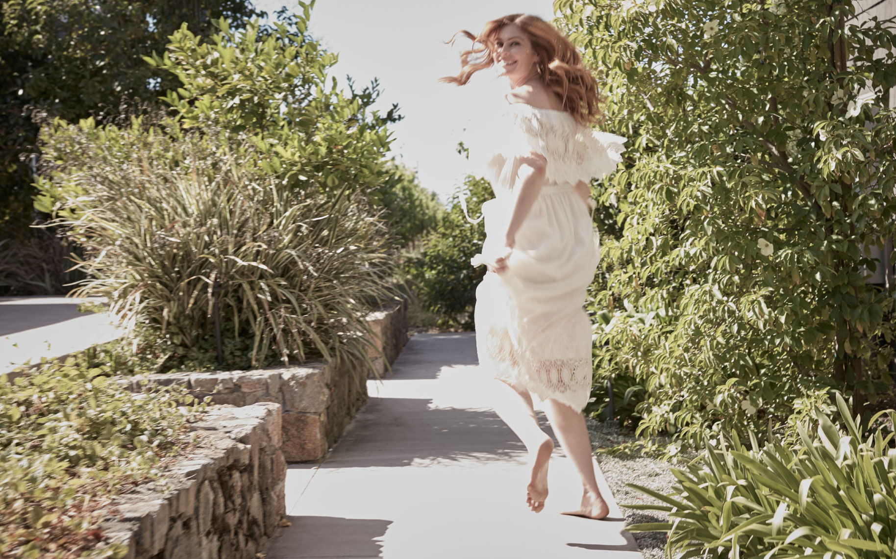 Playful woman running  in a white dress on path in a shot for Senza Hotel and Spa in Napa California