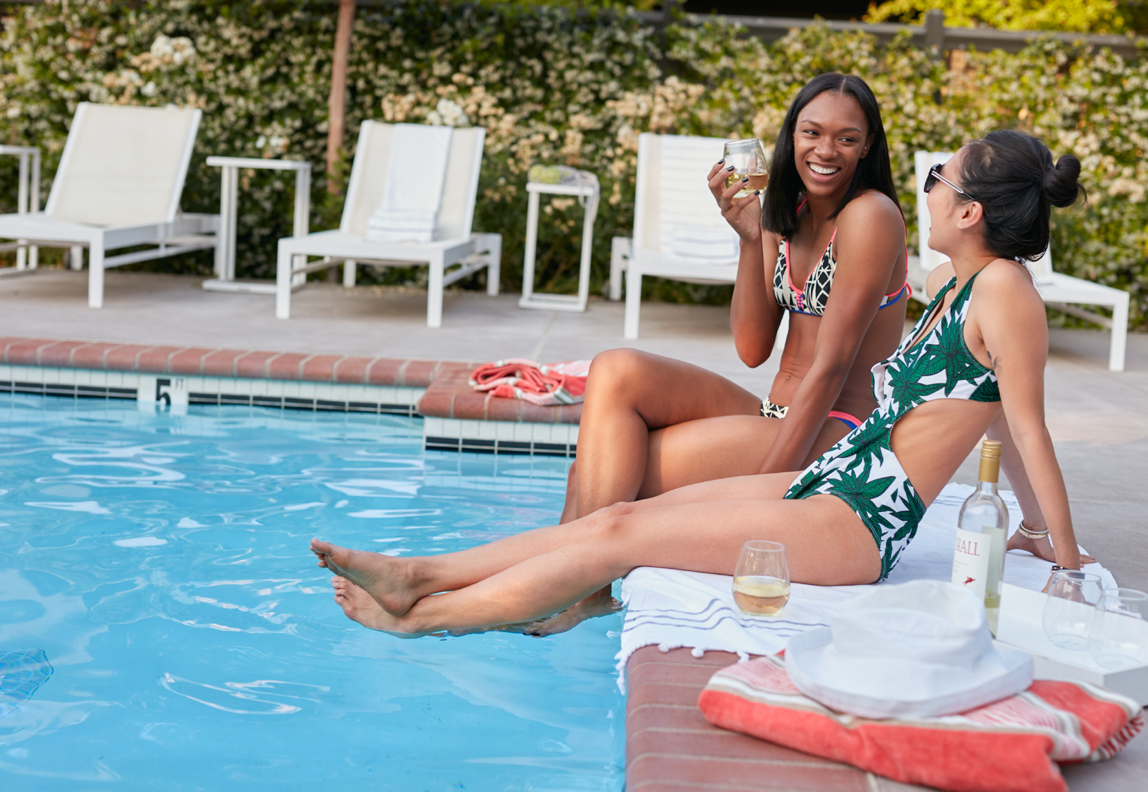 Two women laughing with their feet in a blue pool  shot for Senza Hotel and Spa in Napa California