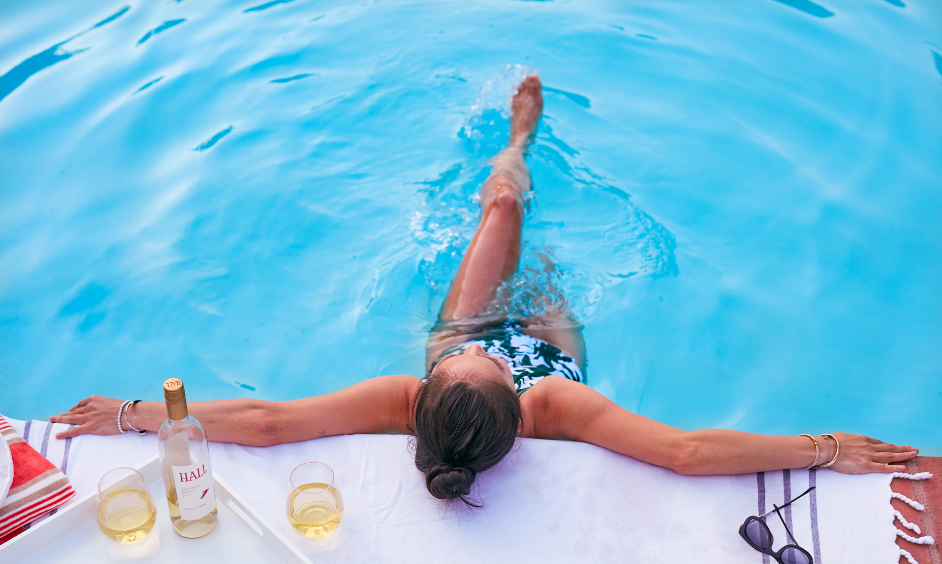Woman relaxing in water at edge of pool with leg at the surface of the pool white wine  and sunglasses at edge of pool in Napa California at Senza Hotel and spa