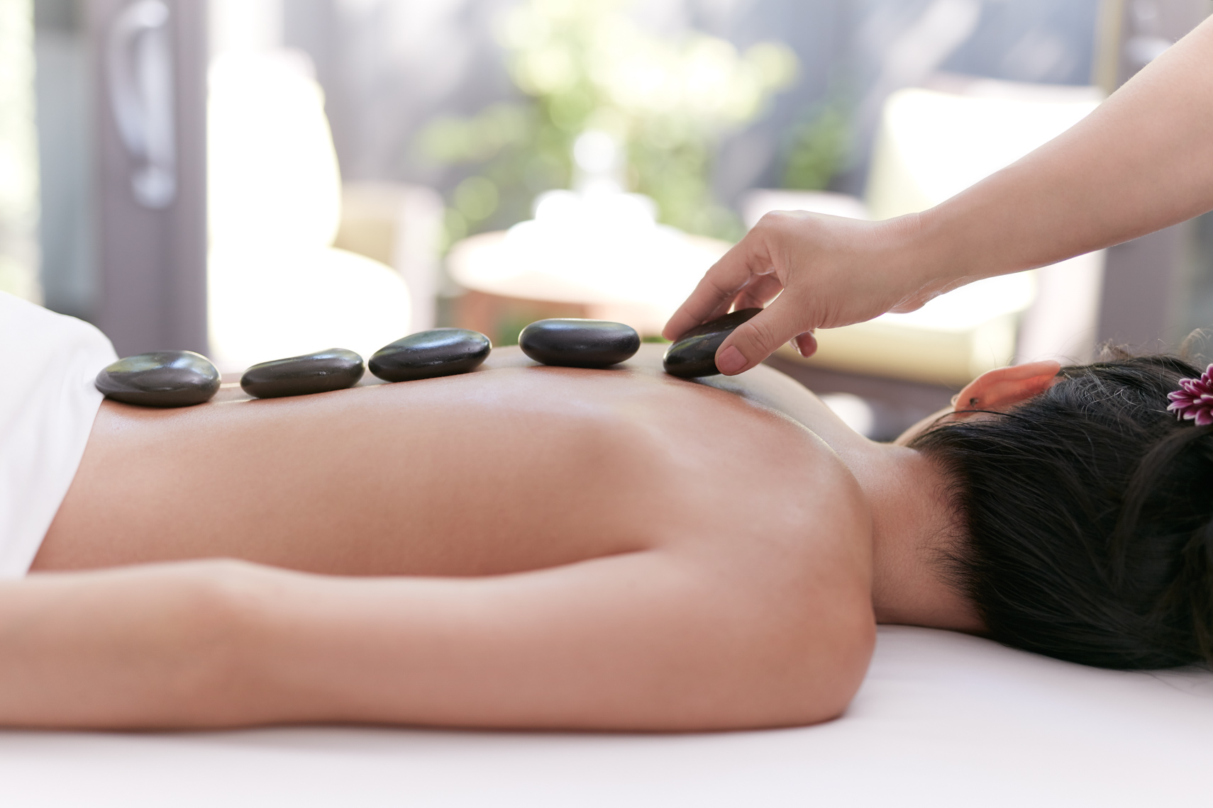 Asian woman laying on massage table while black river stones are being placed on her naked back