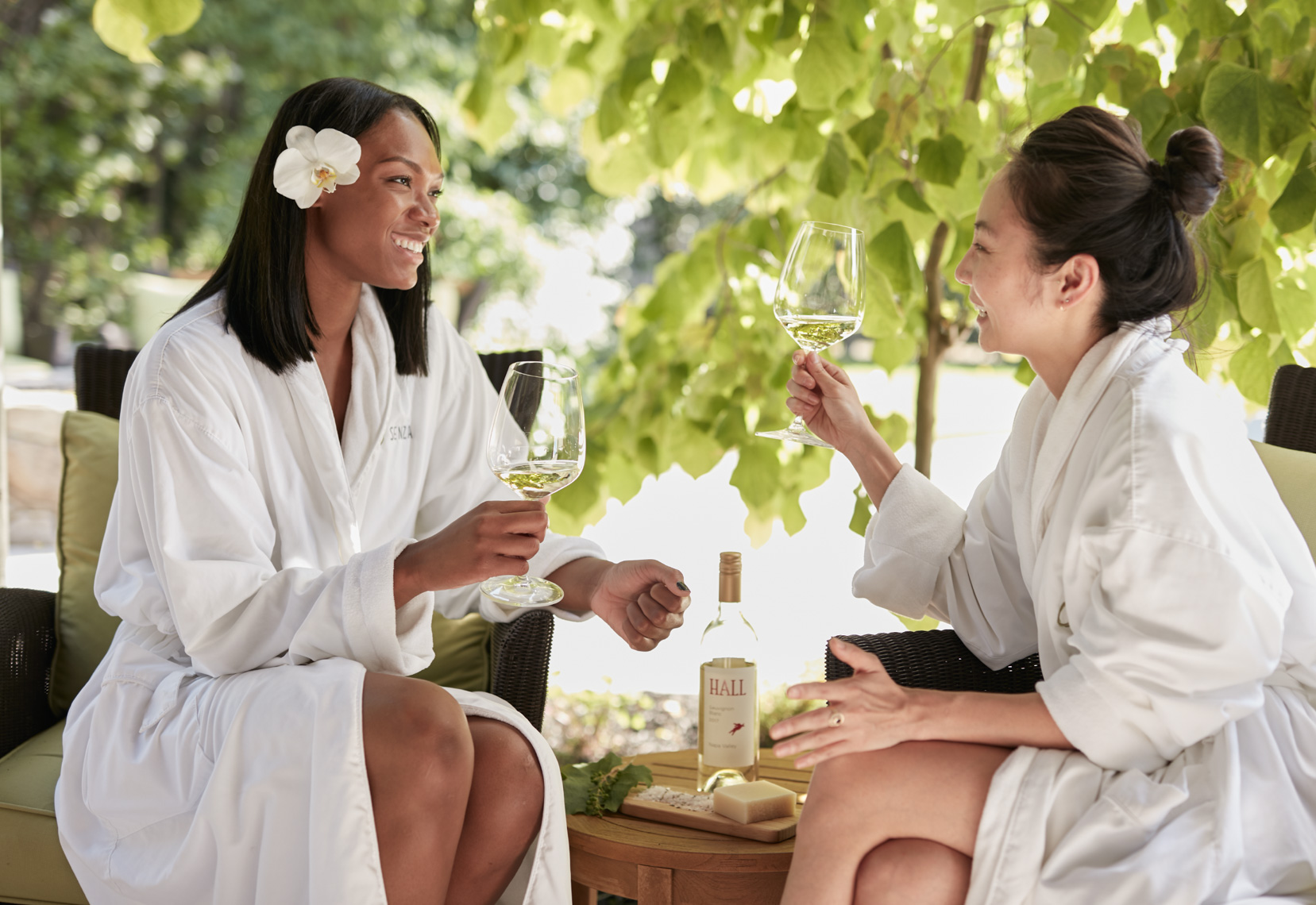 Two women wearing white spa robes talking in the garden and drinking white wine