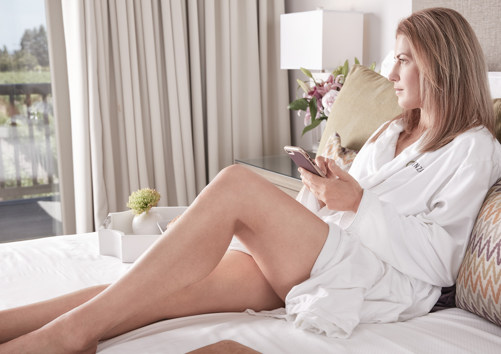 Woman in robe with bare legs reading smart phone in hotel bed in wine country San Francisco lifestyle photographer