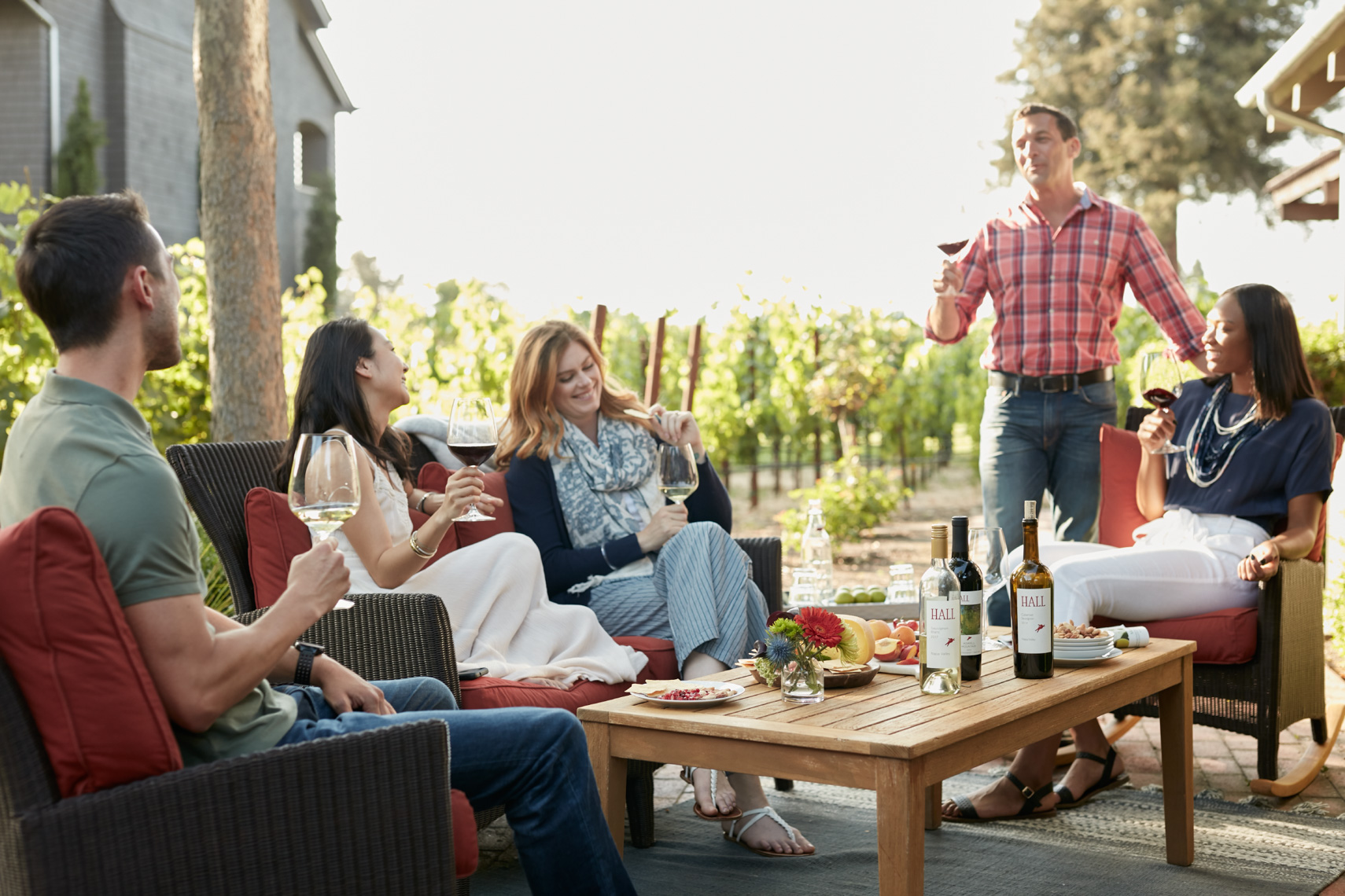 Outdoor party of 5 people enjoying wime near the vinyards  shot for Senza Hotel and Spa in Napa California