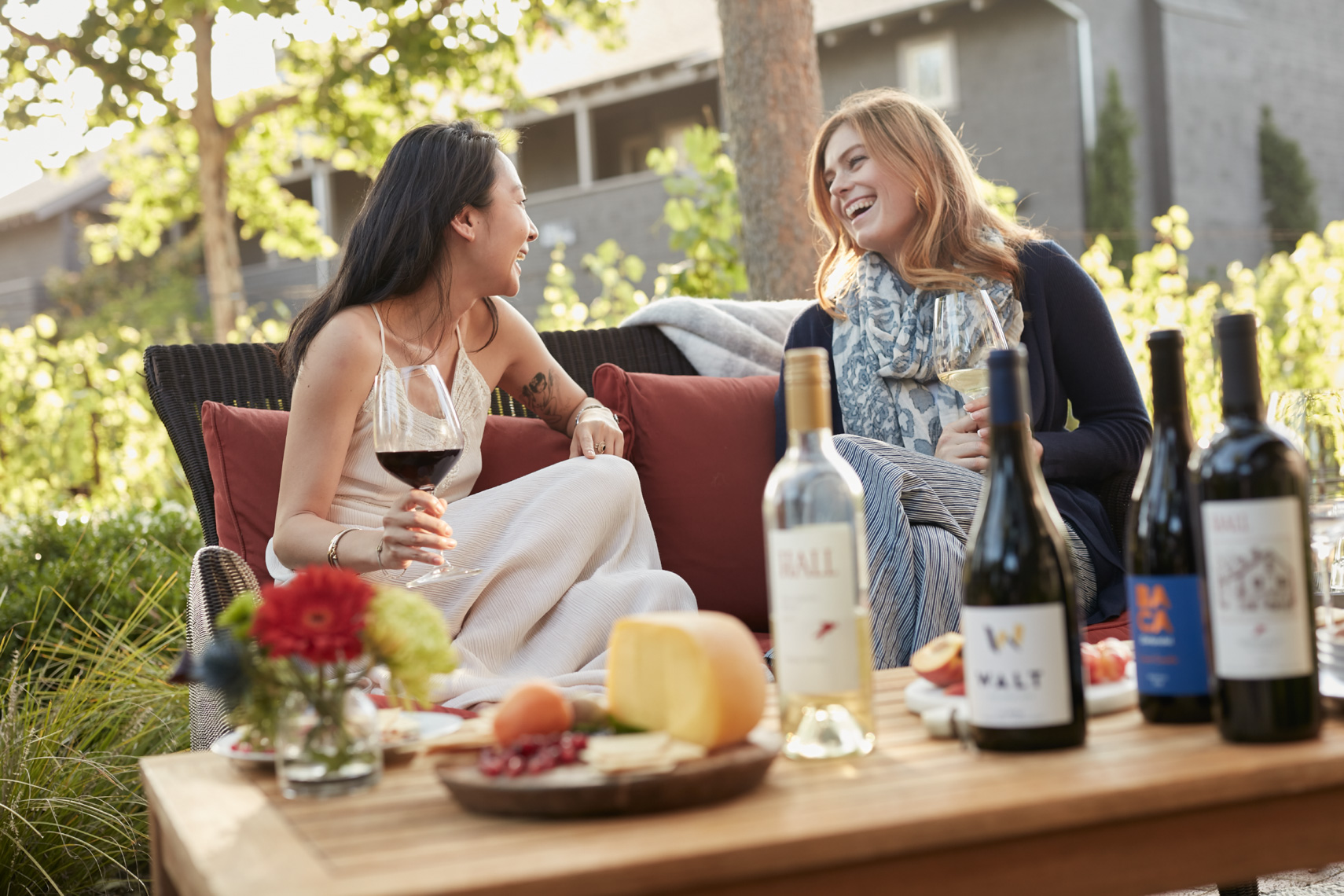 Two women talking and enjoying wine and cheese near the vinyard at Senza hotel in Napa California.