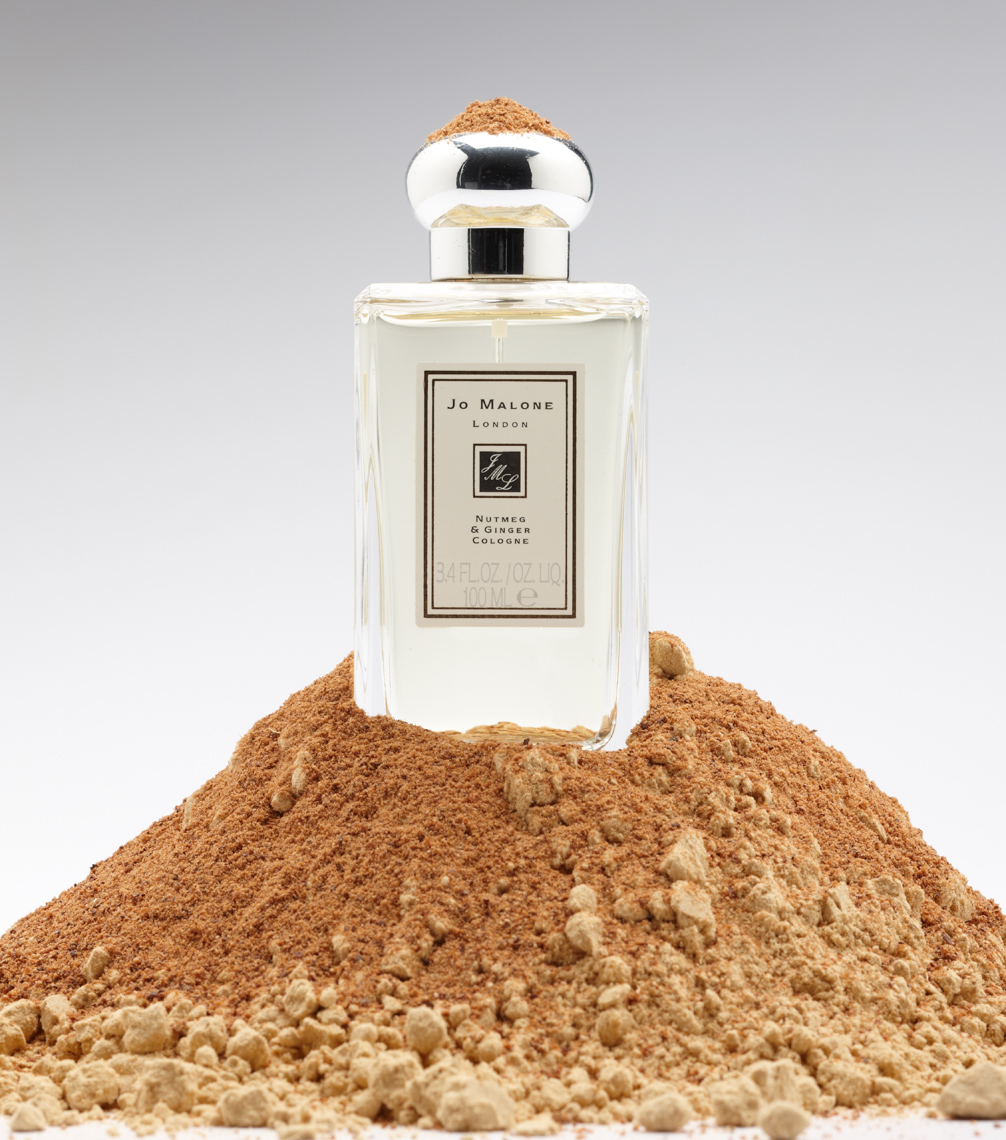 clear perfume bottle sitting on mound of cocoa powder