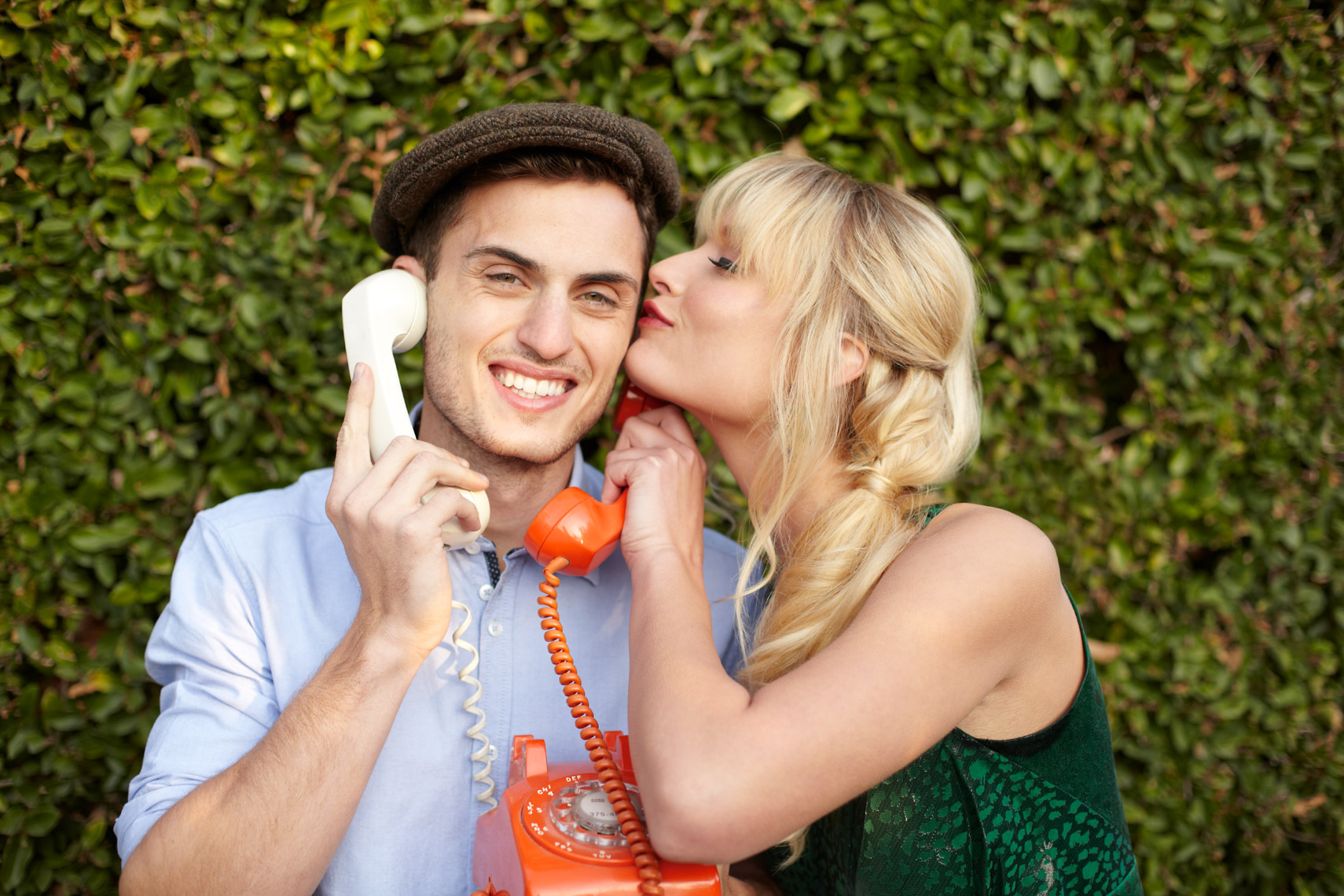 Woman kissing man in hat on the cheek while he talks on vintage phone outside