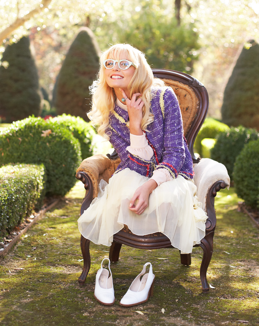 Blond woman white dress curled up on vintage wood chair in garden San Francisco lifestyle photographer