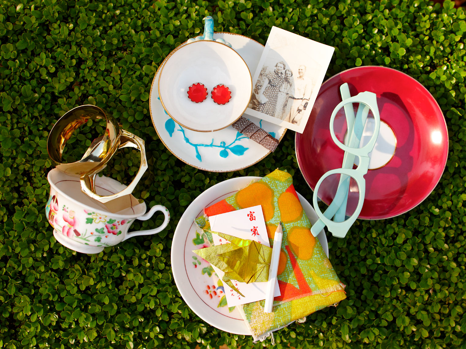 Still life of cups and plates and bracelets on green hedge