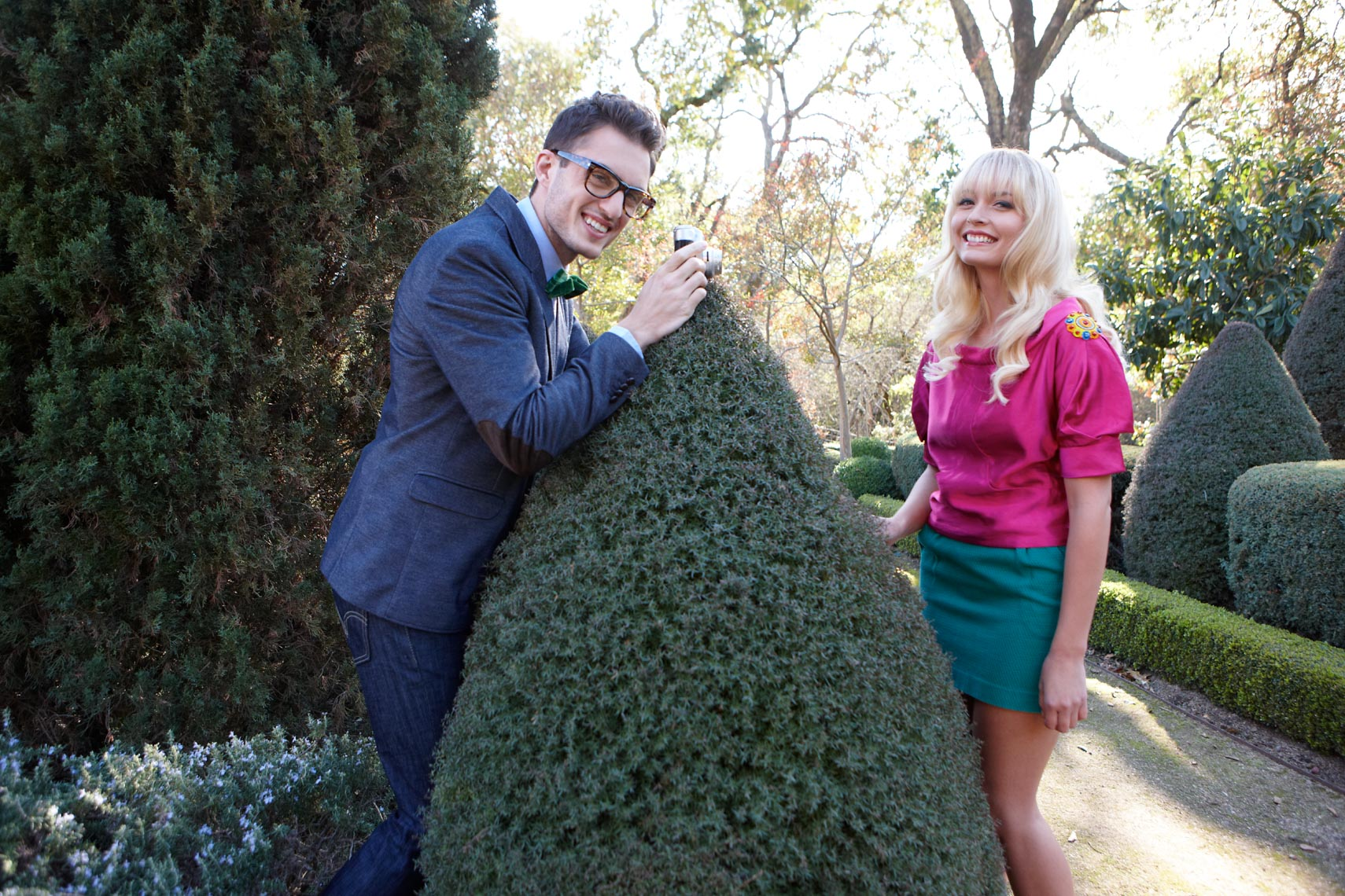 Formally dressed young couple snapping photos of each other in a topiary garden