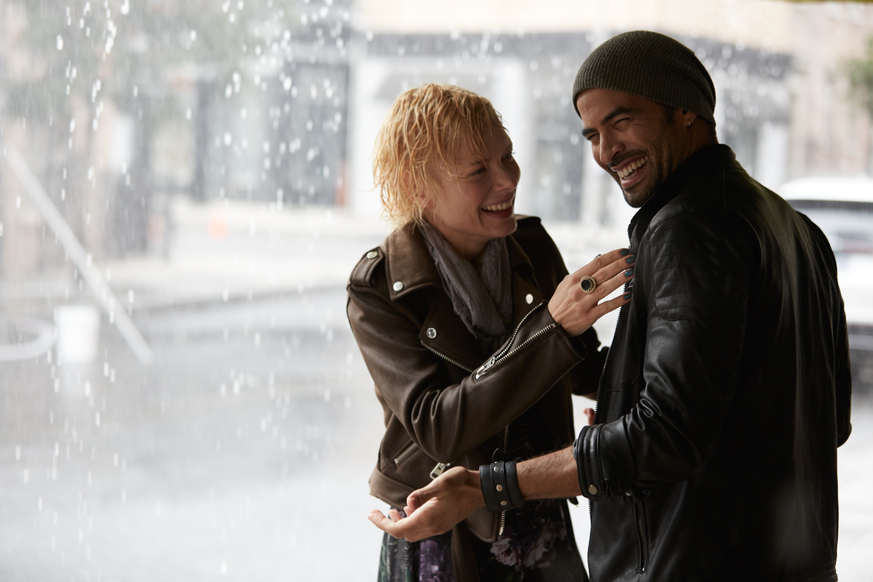 Woman and man wearing leather and laughing at each other on the sidewalk on a rainy day