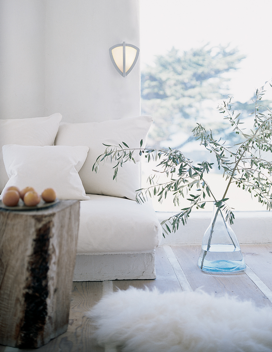 Living room with white couch next to an olive branch in a blue sea glass vase