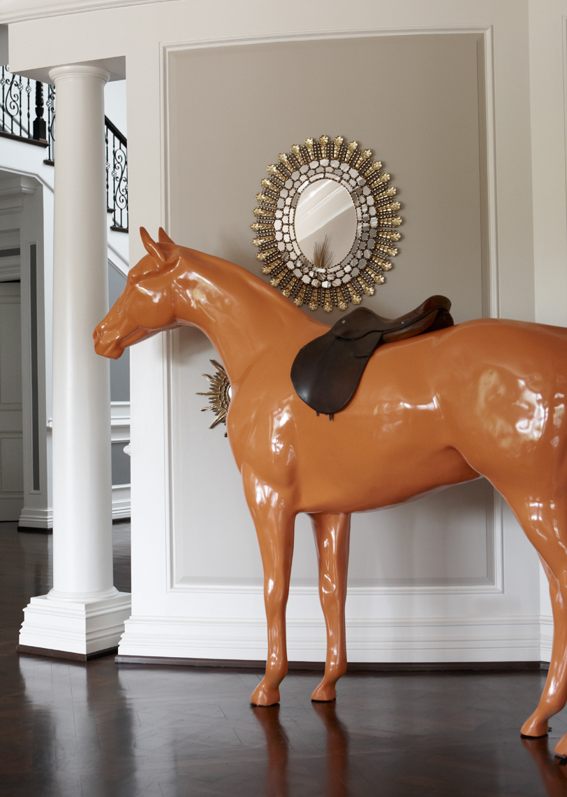 life-size orange horse sculpture on wooden floor in home entryway