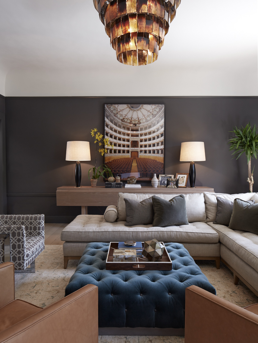 living room interior with dark grey walls and grey sofa and furniture surrounding square blue ottoman
