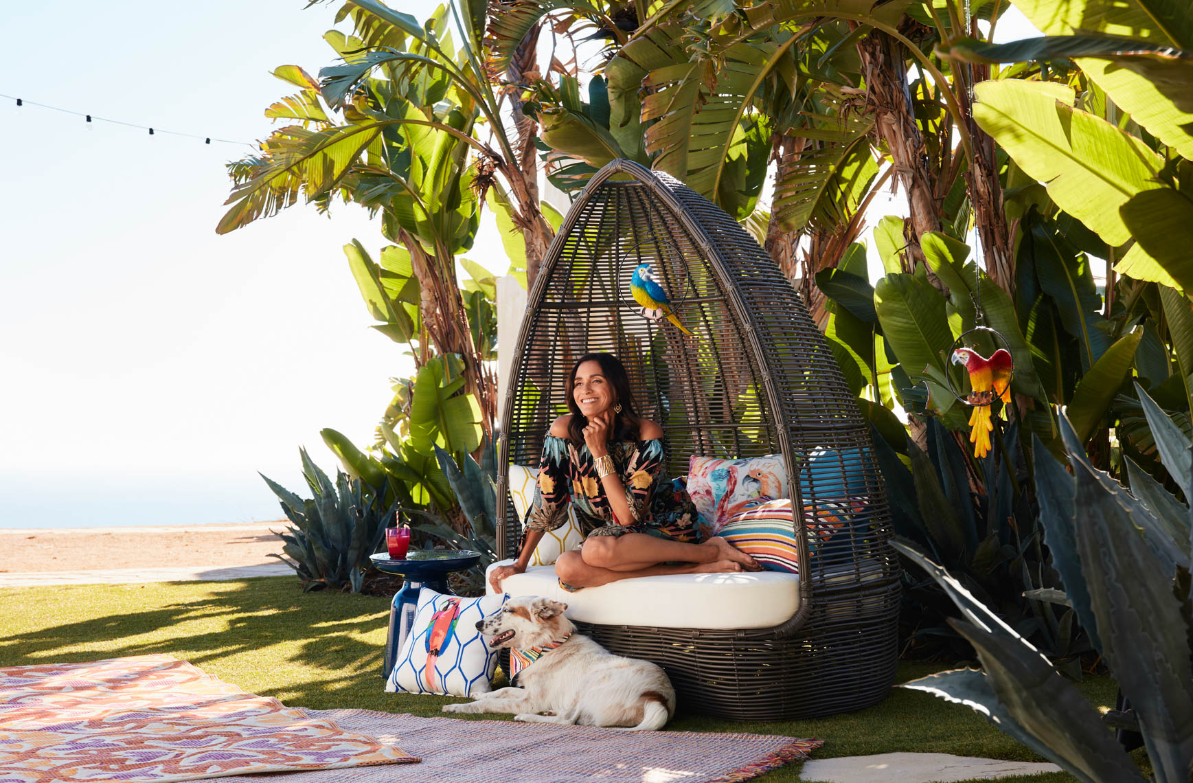 Woman seated in egg chair in grass with white dog in lush parlms near the beach San Francisco lifestyle photographer