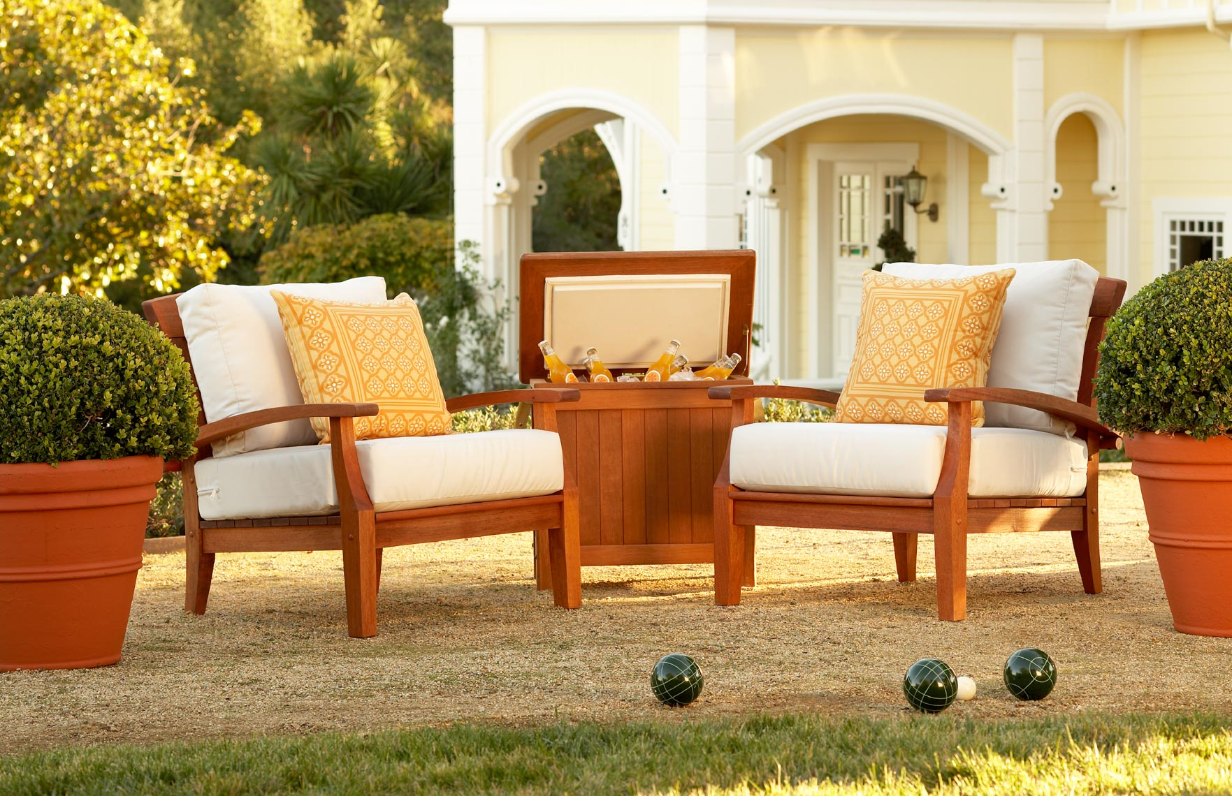 Teak chairs and cooler by green grass