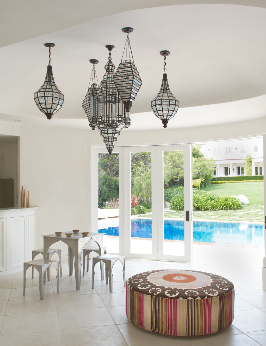 white tiled moroccan home interior with round decorative cushion and sliding glass door view of pool and garden