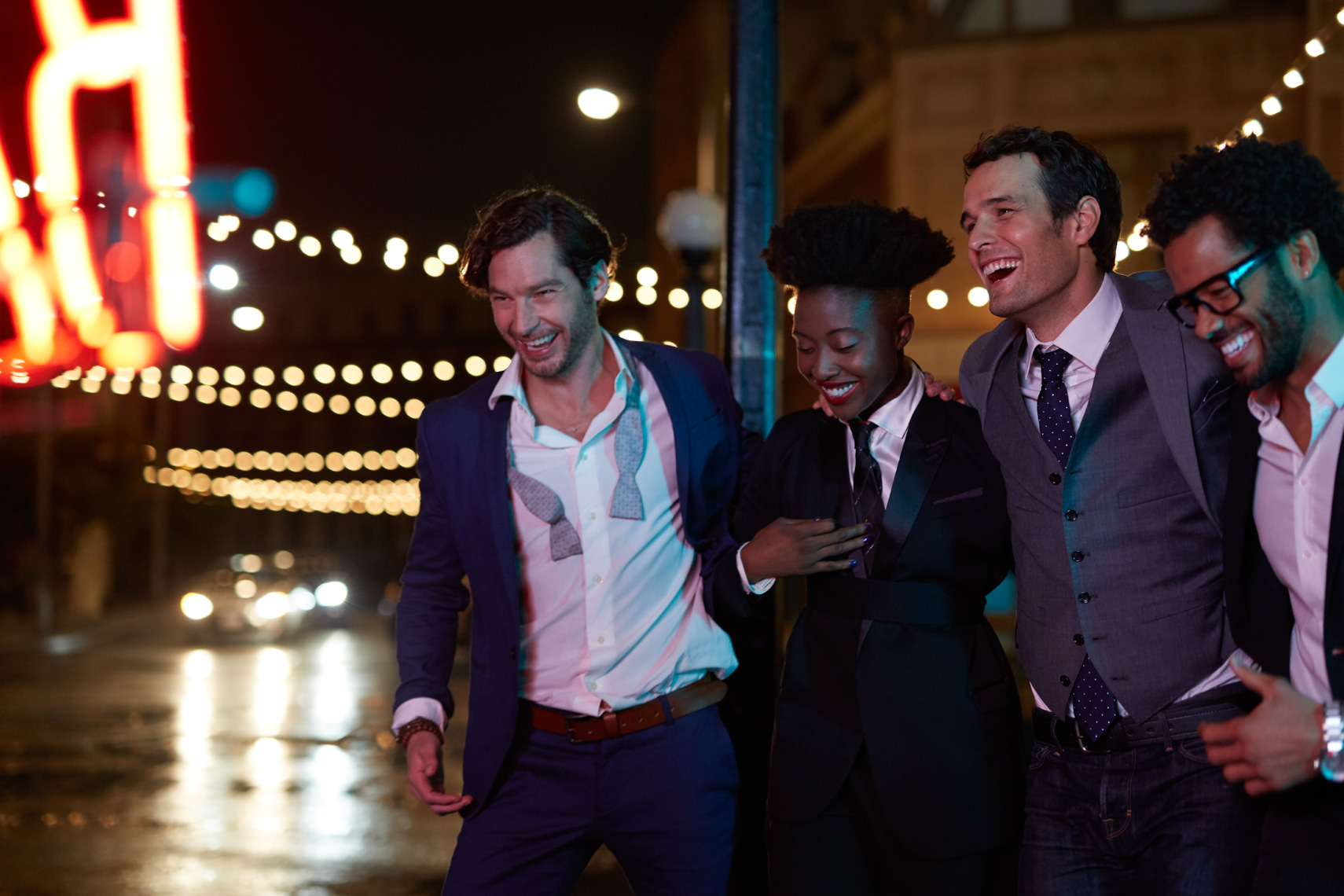 Four men and woman dressed formal  out on the town at night laughing and celebrating while walking past lights