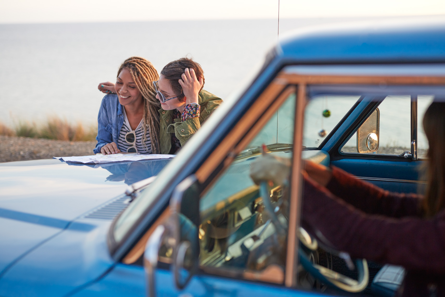 Two women looking at a map on the hood of a vintage American car along a coastal road in California San Francisco lifestyle photographer
