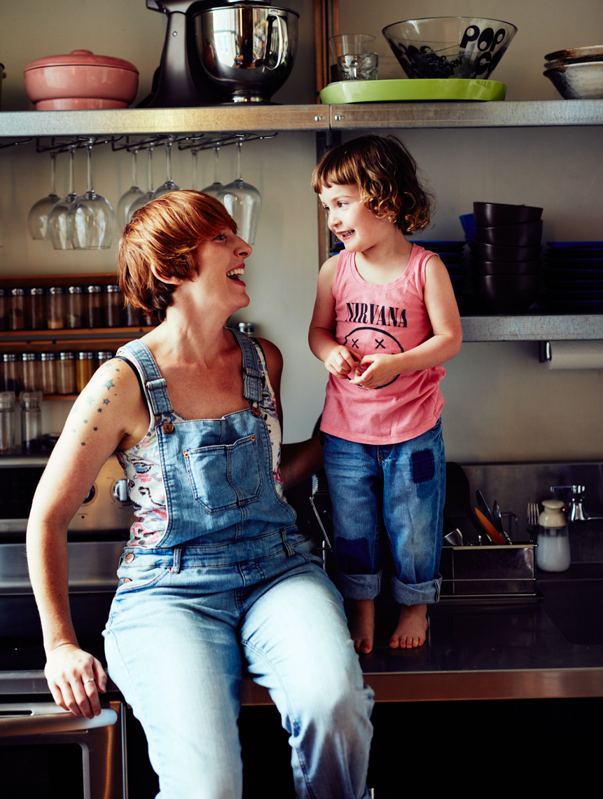 Mother wearing overalls and looking and smiling at daughter standing on kitchen counter San Francisco lifestyle photographer