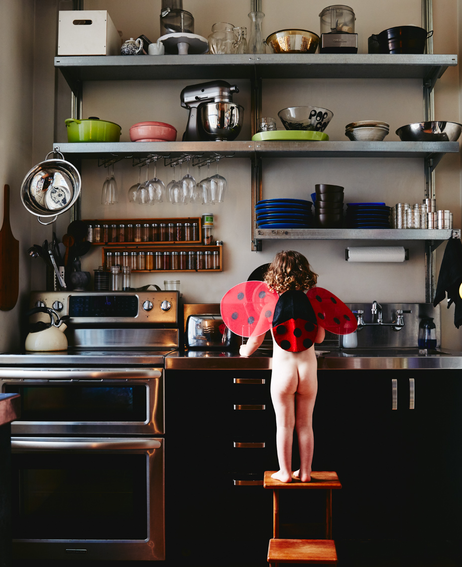 Todler standing on step stool with bare bottom and back to camera wearing red and black ladybug wings in the kitchen