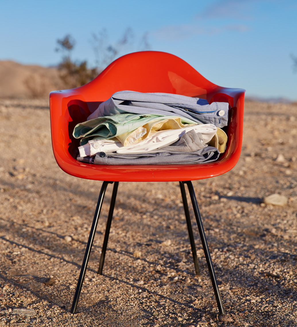folded colored pants on red chair with desert scene San Francisco product photographer