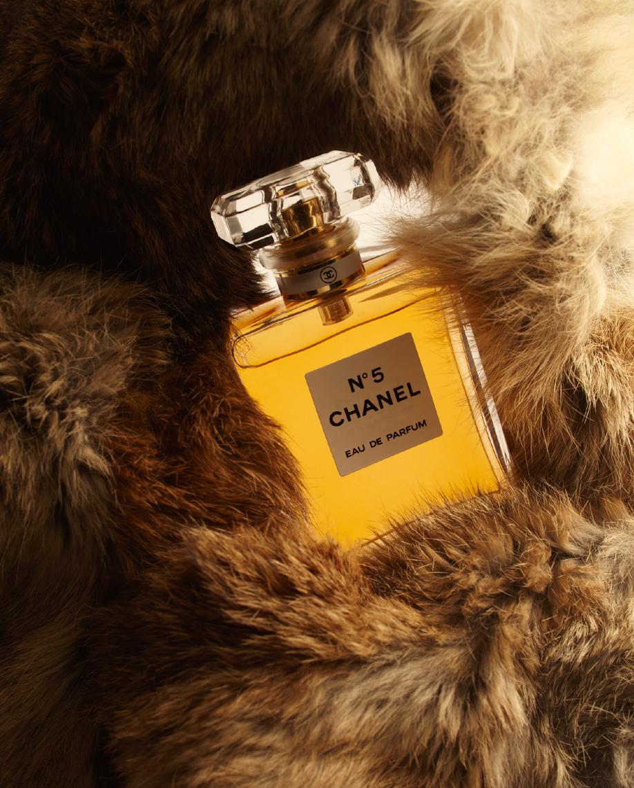 yellow Chanel perfume bottle on fur coat