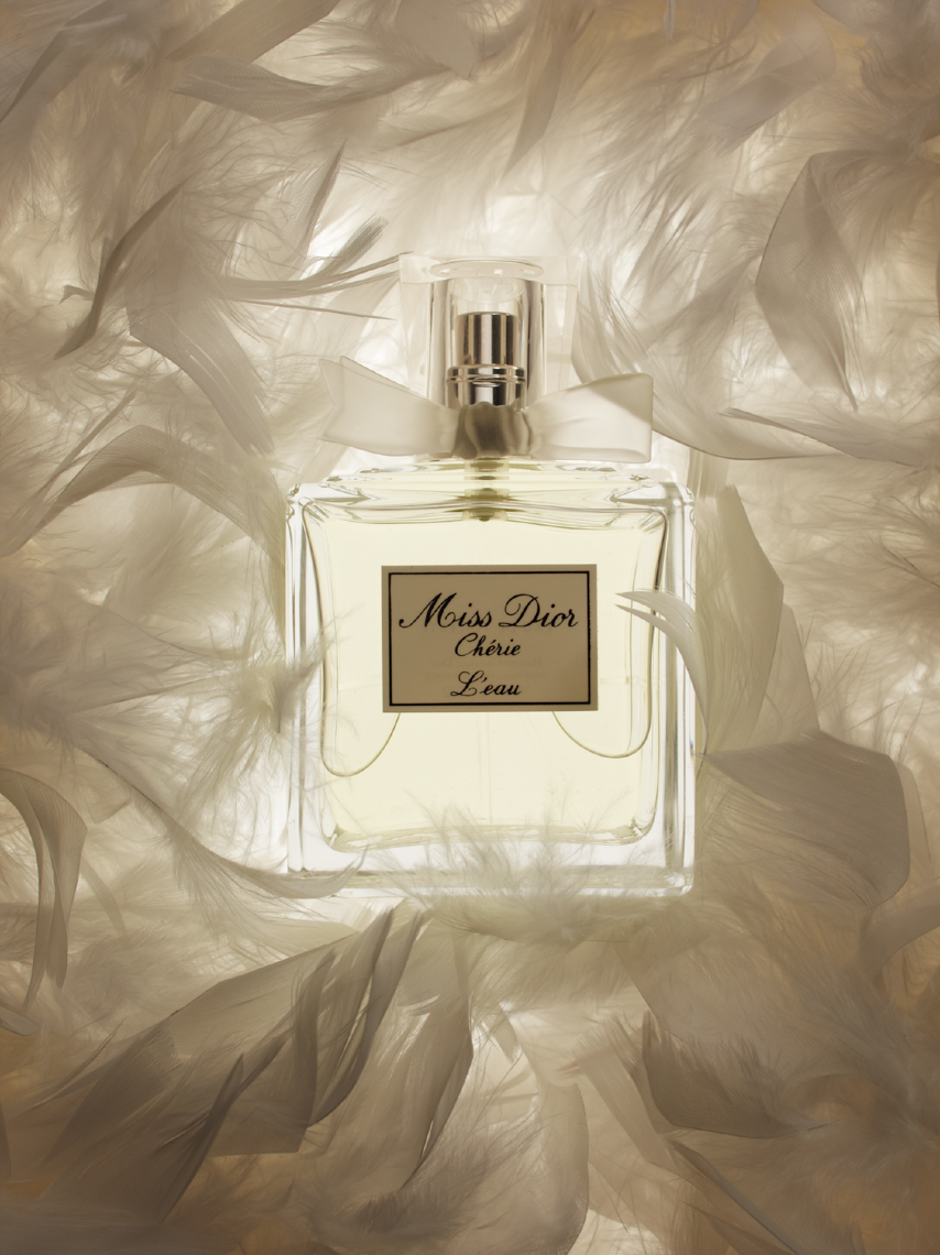clear perfume bottle on white feathery surface