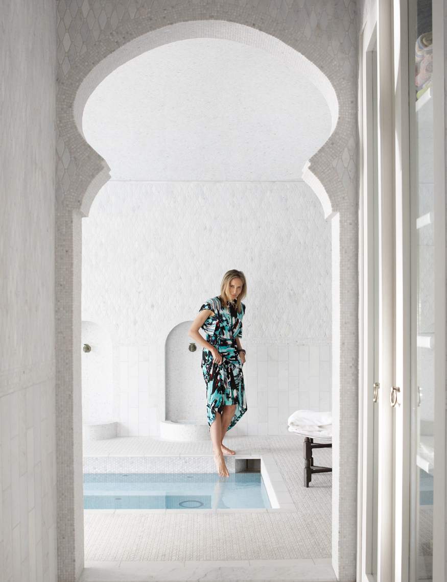 woman in blue sundress dipping her toe into white marble moroccan pool