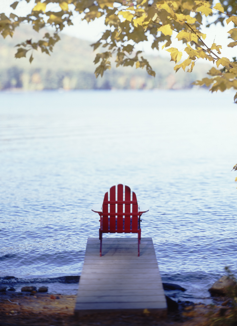 Red adirondack chair on narrow dock on lake in Maine
