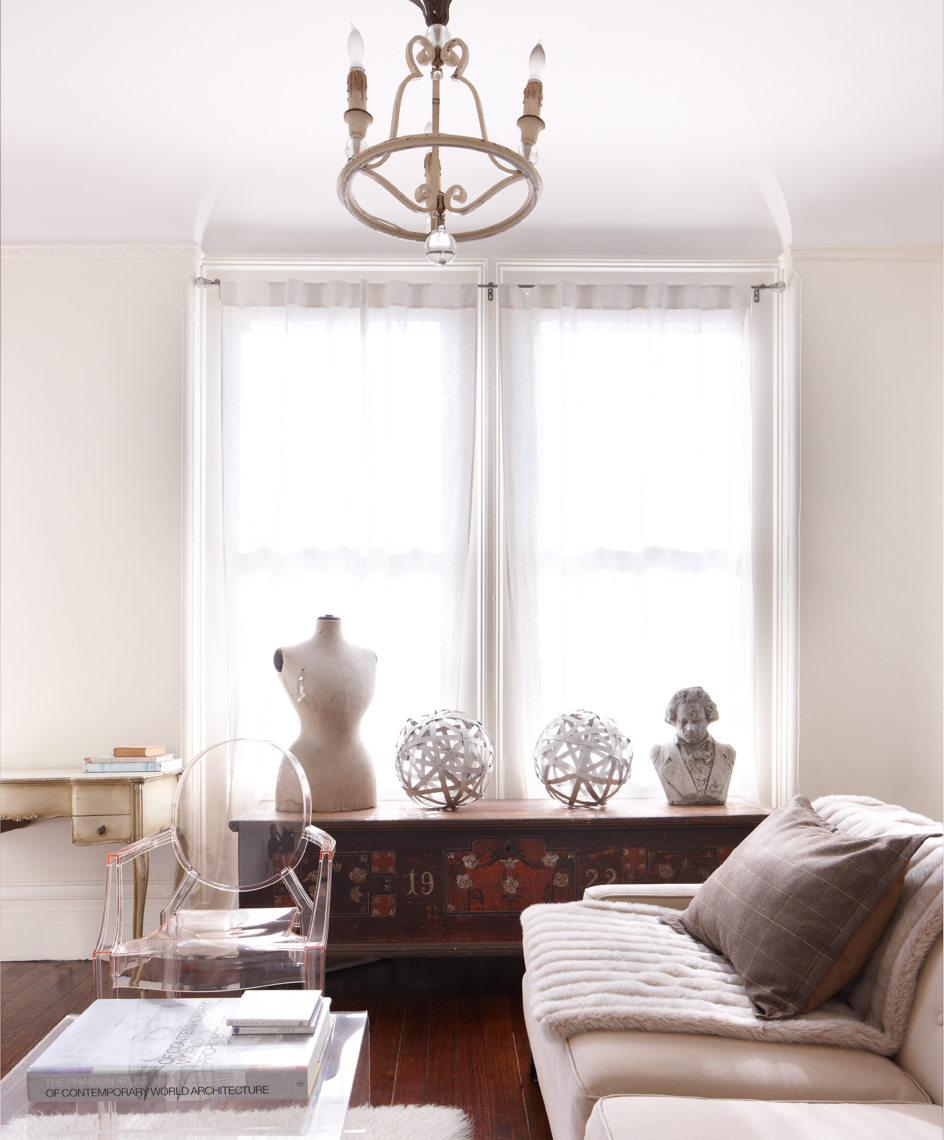 living room interior with white sofa and plexiglass chair and decorative white sculptures on windowsill