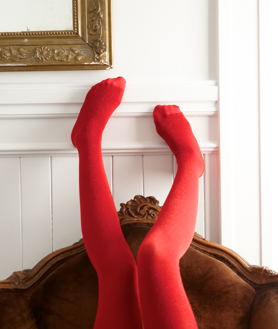 Red stockinged legs playfully against a white wall with wood and fabric formal chair below