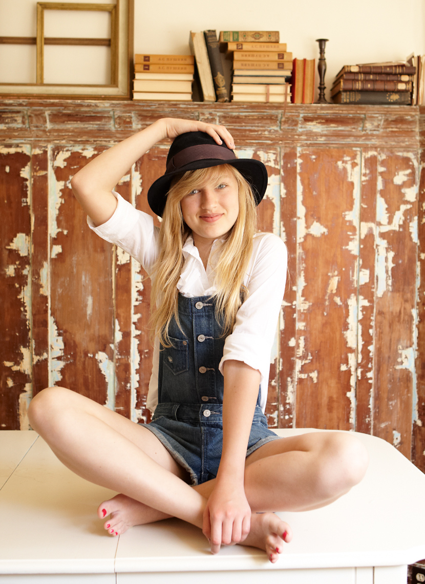 Vibrant smiling blond girl sitting on a table cross-legged with her hand on her black hat