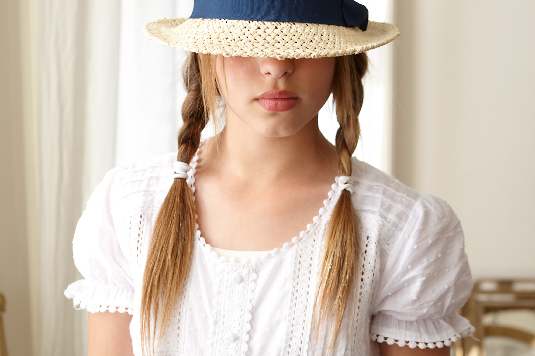Found girl with pigtails wearing white blouse and a hat tipped down over her eyes San Francisco lifestyle photographer