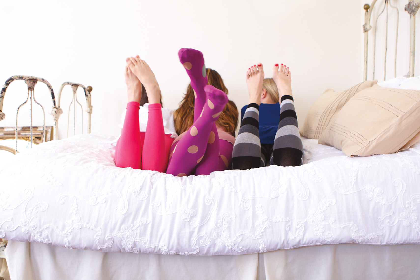 Three girls in colorful leggings laying on white bed with feet up in the air