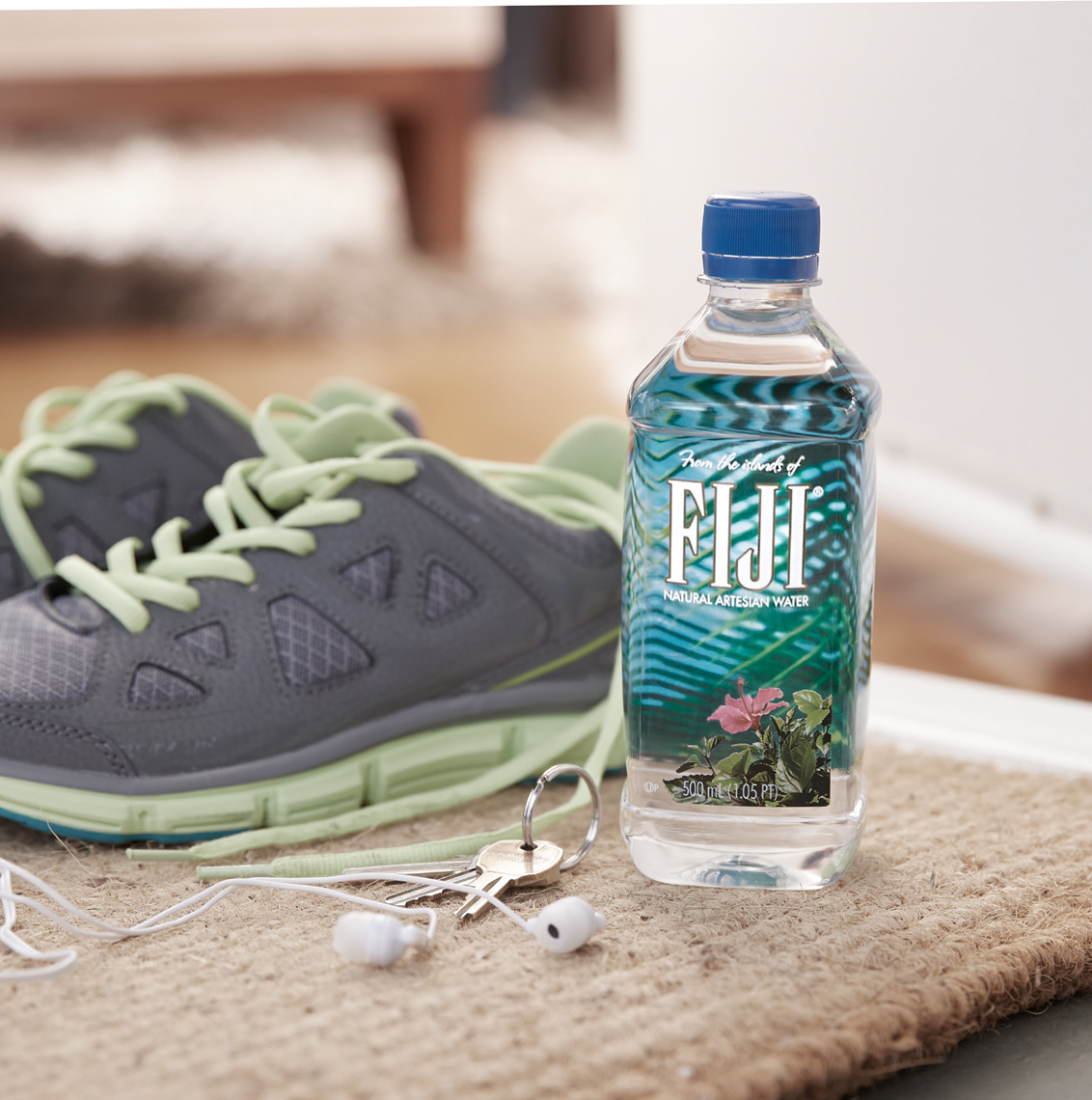 Fiji bottled water next to running shoes and earbuds