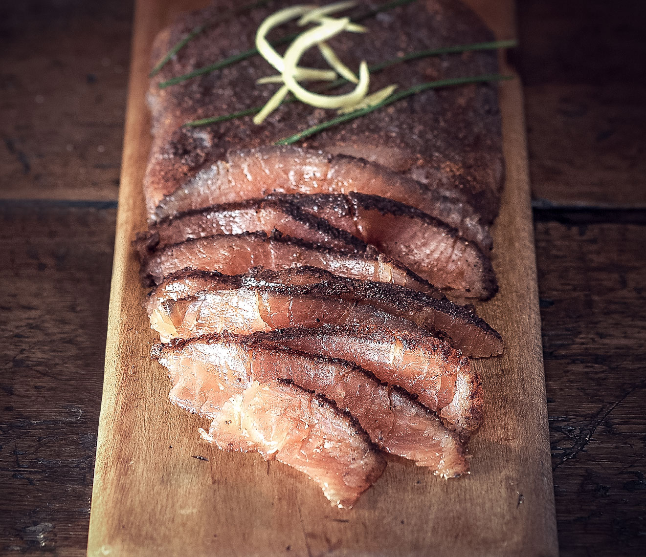 thinly sliced and seasoned smoked salmon on wooden surface