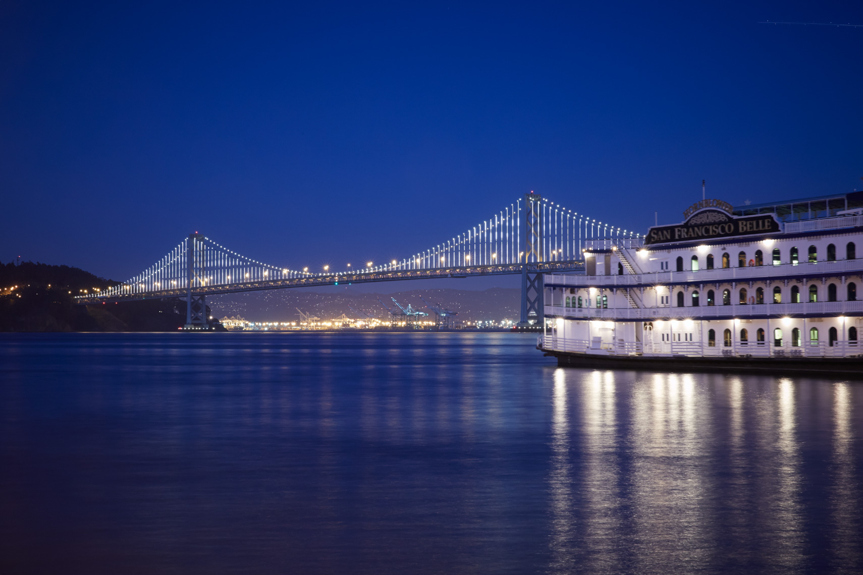 Oakland Bay Bridge viewed from San Francisco city water front at dusk with lights on bridge and ferry boat
