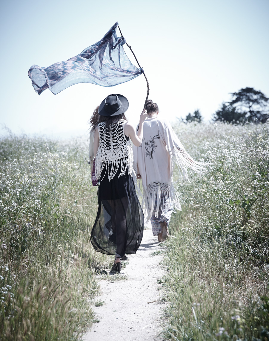 Three hipster girls walking along a coastal path waving a flag of blue cloth