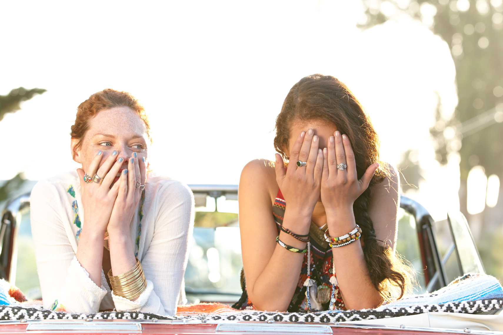 Two young women smiling over the back of a convertible car with the top down and hands covering their faces